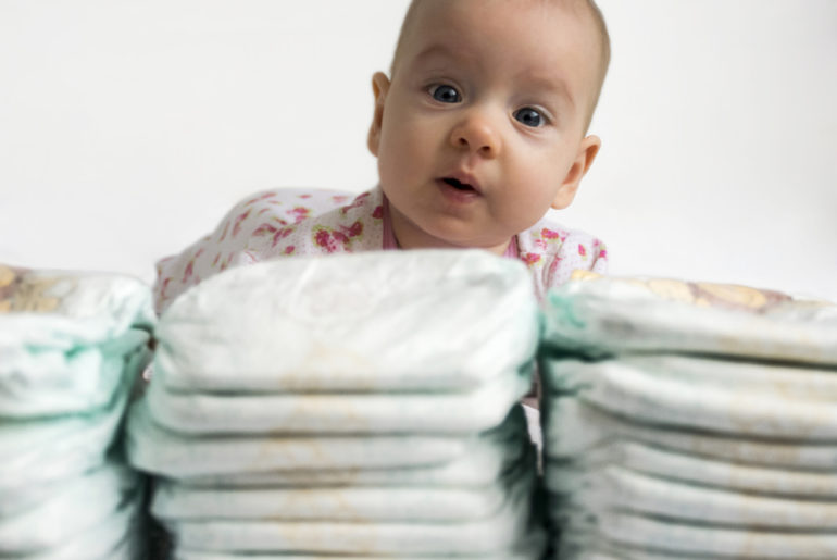 Adorable baby girl looking over a stack of diapers