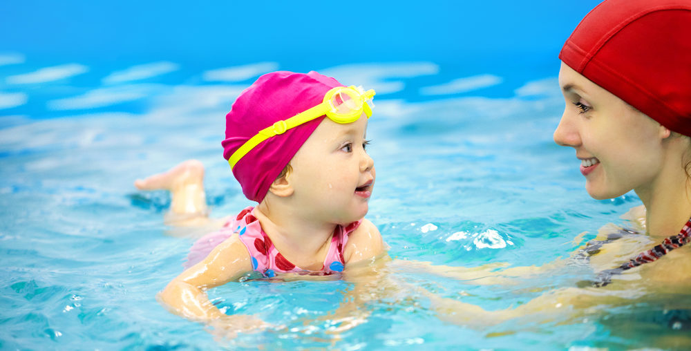 child swimming with mother